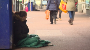 A rough sleeper sitting in the street.